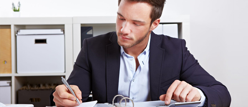 Professional Business Administrator working at his desk, writing in a binder.