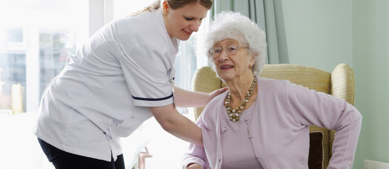 Health Care Assistant helping an elderly patient sit down in a comfortable chair.