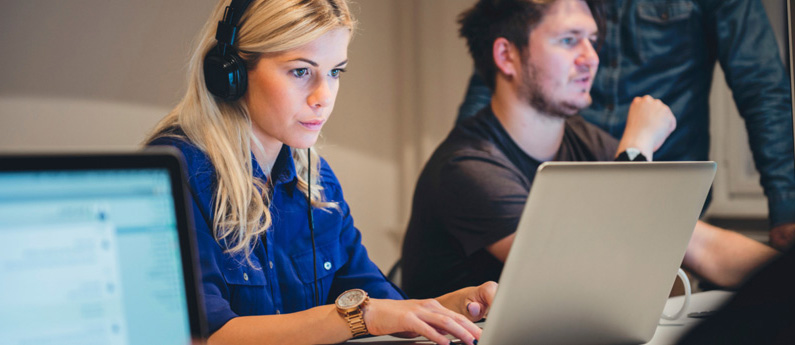 Web Development professionals working at their computers. The woman in front is wearing headphones.