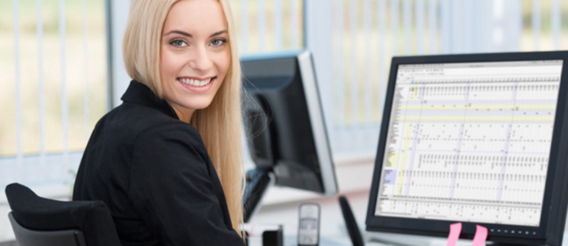 An office professional sitting in front of her computer. She is turned towards the camera and smiling over her right shoulder.
