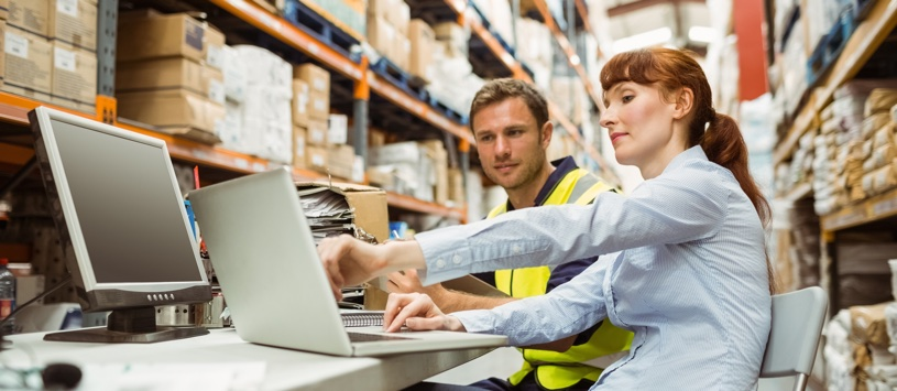 Logistics Manager sitting with colleague in warehouse